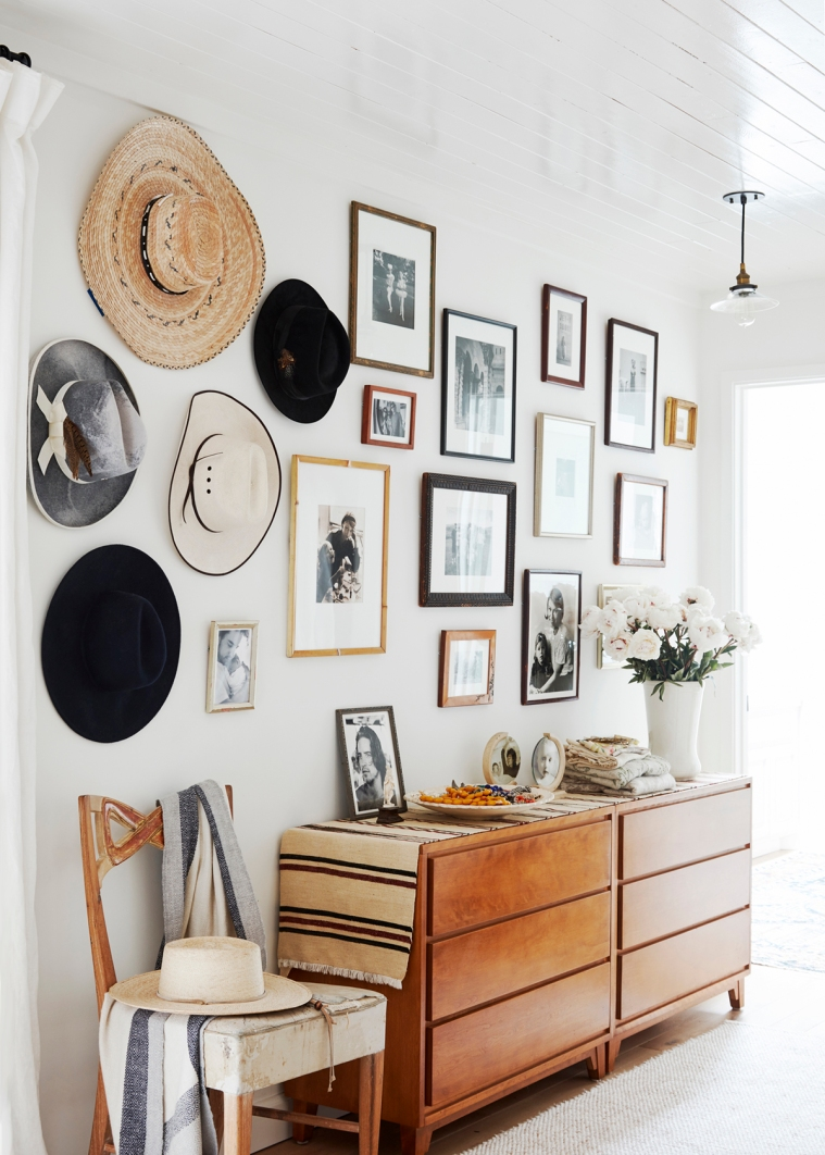 a-collection-of-hats-and-art-surround-the-dresser-in-the-bedroom-relaxed-ranch-house-tour-on-coco-kelley
