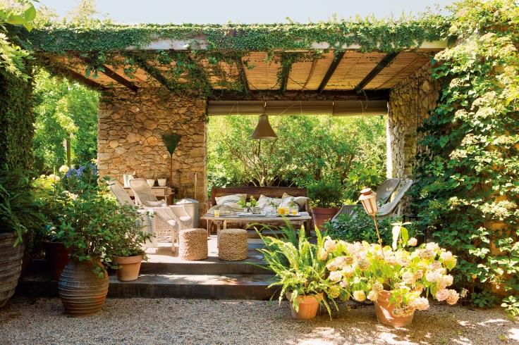 pergola-con-techo-de-canizo-y-paredes-de-piedra-en-jardin_a783a6e7